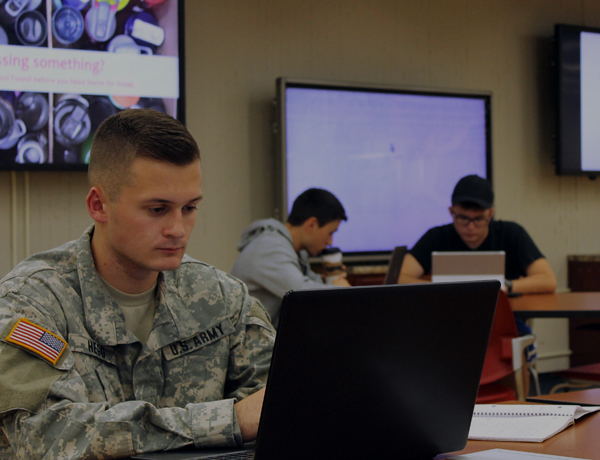 Student in Military uniform studying in the library.