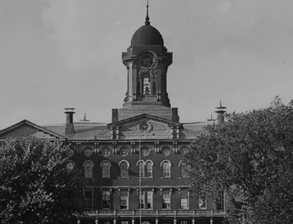 A historic black and white photograph of the original Old Main building with it's bell tower.