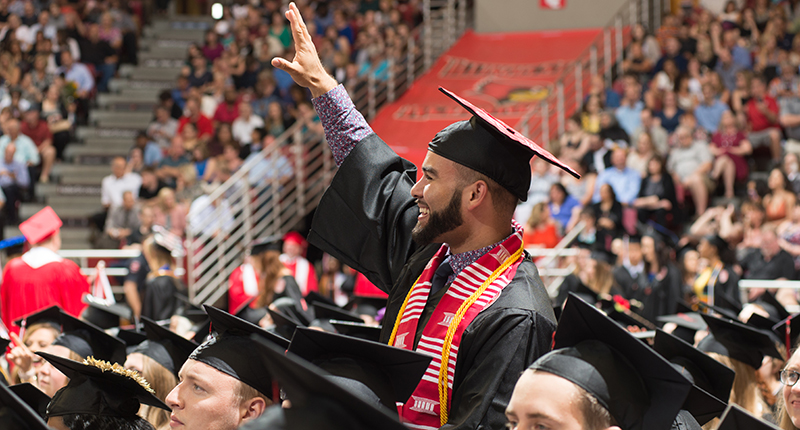 Male in cap and gown standing in arena, waving at crowd.