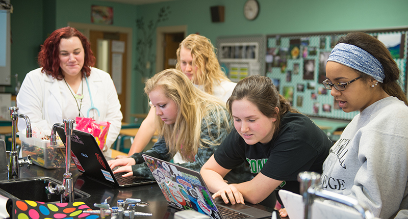 Four girls in a college of nursing lab looking at computers.