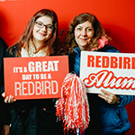 Mother holding alumni sign and daughter holding Redbird sign.