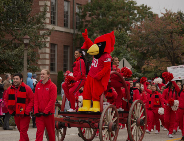 Reggie the Redbird stands on a chariot among cheerleaders during the Homecoming Parade.