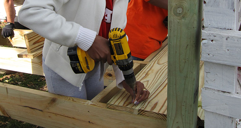 Student using a drill to help build a home.