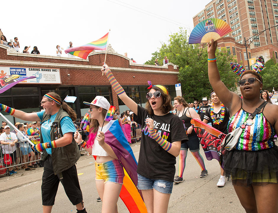 Students walking on the street in bright colors, cheering during the Chicago Pride Parade.