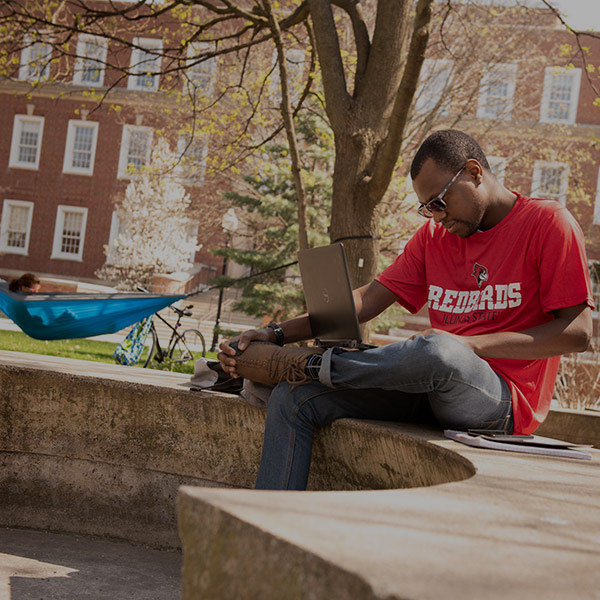 Student sitting on a concrete bench on the quad.