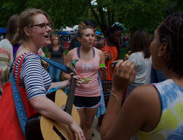 A group of students playing instruments and singing on the quad.