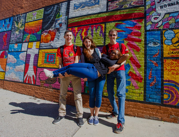 Students pose in front of the mural in Uptown Normal.