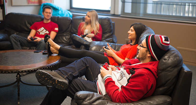 International students relaxing on a couch, playing video games.