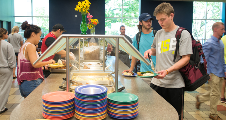 students filling their plates at the dining center