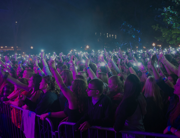 Students shining their cellphones at a concert on the quad.