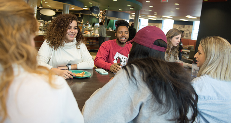 Group of students talking and eating at a table in the Watterson dining center.