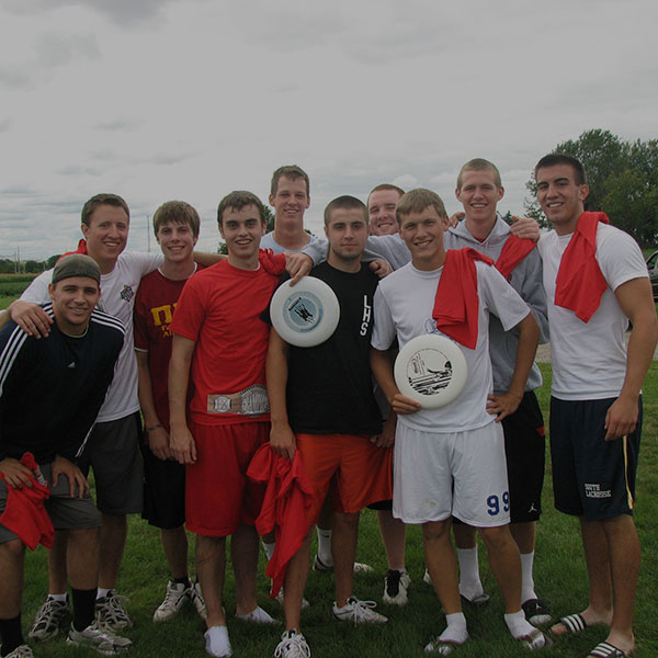 A frisbee team posing for a photo after practice.