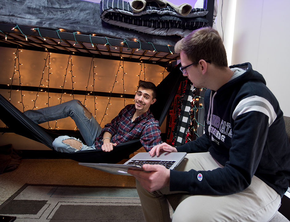 Two boys in a residence hall, one in a hammock under a loft bed and another sitting in a desk chair with a laptop.