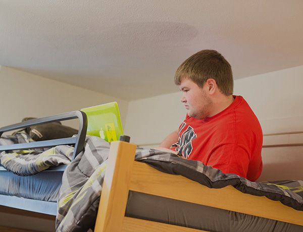 Male student laying on a lofted bed with his laptop.